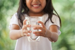 Cute asian little girl holding glass of fresh water in green nature background