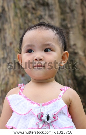 Cute Asian little girl looking up. Sweating on hair after playing.