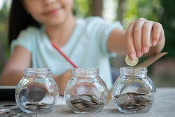 Cute asian little girl playing with coins making stacks of money,kid saving money into piggy bank, into glass jar. Child counting his saved coins, Children learning about for the future concept.