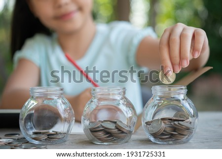 Cute asian little girl playing with coins making stacks of money,kid saving money into piggy bank, into glass jar. Child counting his saved coins, Children learning about for the future concept. Foto stock ©