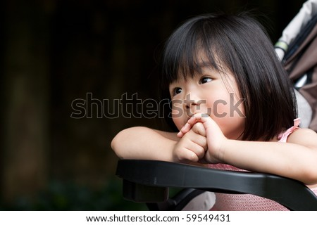 Cute Asian little girl smiling and with both hands holding together