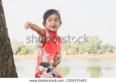 dd4f2fe1fcd8e Cute Asian little girl wearing Chinese traditional dress smiling over a  park landscape background. Happy