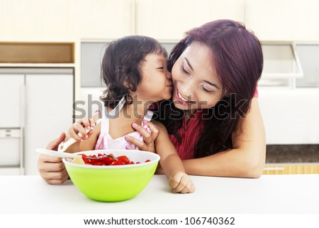Cute asian little girl with fruit salad kissing her mother. shot in the kitchen