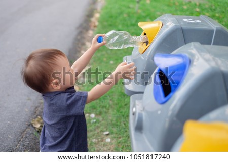 Cute Asian 18 months / 1 year old toddler baby boy child throwing plastic bottle in recycling trash bin at public park, Eco friendly Save the world concept, Selective focus at bottle & kid's hand