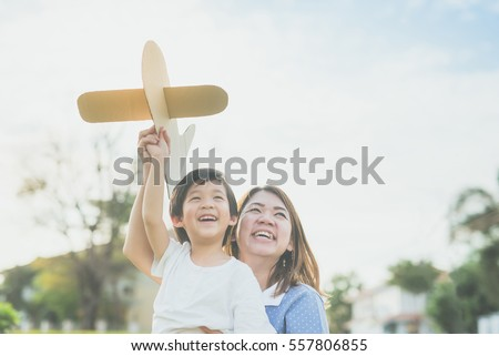Cute Asian mother and son playing cardboard airplane together in the park outdoors