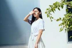 Cute asian woman facing the sun outdoor near plant branch.