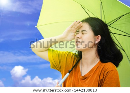 Cute asian women use their hands to covers her face from the sun and holding umbrella with sunlight and blue sky and Cloud background in the hot weather In summer #1442138810
