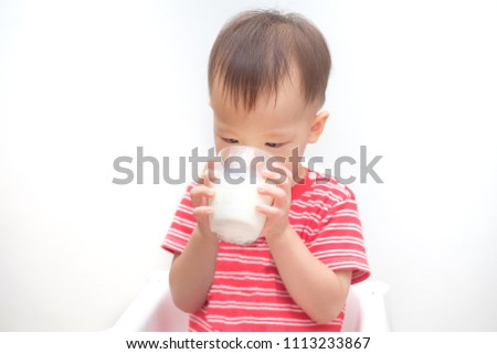 Cute Asian 2 years old toddler baby boy child drinking milk from a glass, Little kid sitting in high chair holding glass of milk at breakfast time isolated on white, Best drinks for toddlers concept