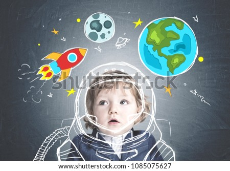 Cute astonished little boy in a suit standing near a blackboard with a bright rocket, Earth and Moon drawings on it. Concept of dreaming and imaginary worlds.