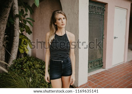130c8c1e07f4 Cute Attractive Blonde Young Woman in Stripes Smiling and Posing for Camera  Downtown #1169635141
