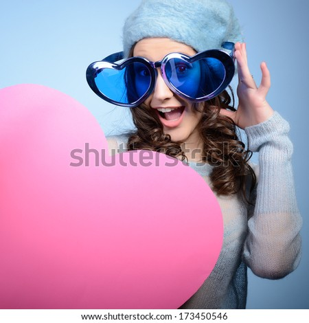Cute attractive fashion young girl posing with funny big love glasses and pink heart over blue background