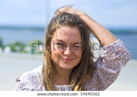 Cute attractive women smiling at the beach. Summer portrait. Blurring background.