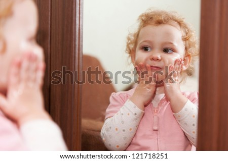Cute baby applying cream on her cheeks looking at mirror