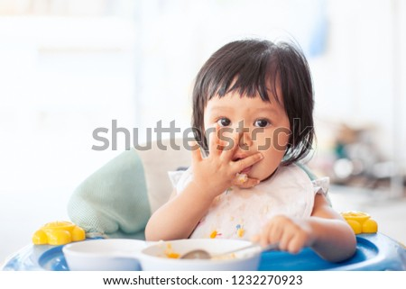 Cute baby asian child girl eating healthy food by herself and making a mess on her face and hand