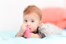 Cute Baby Biting on Calming Teething Toy. Adorable newborn chewing on silicone teether