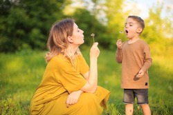 Cute baby boy and mother blowing on a dandelions on green lawn. Summertime photography for ad or blog about motherhood