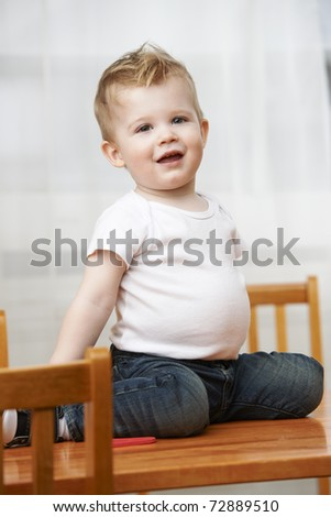 Cute baby boy at 18 months wearing jeans and t-shirt sitting on table at home.