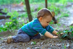 cute baby boy digging the ground in spring forest