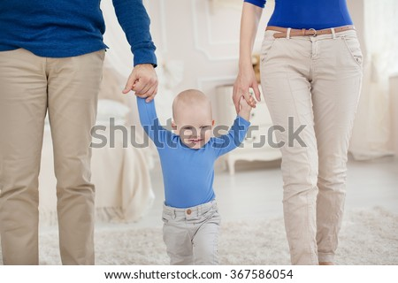 Cute baby boy holding father and mother by the hand and takes first steps