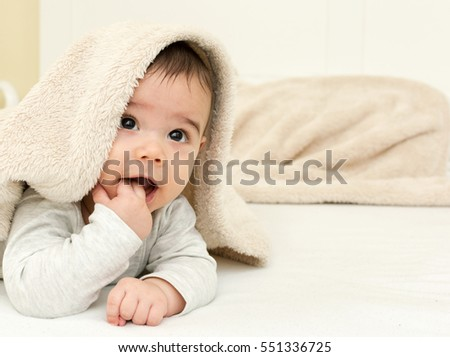 Stock Photo Cute baby boy in bed under a fluffy blanket