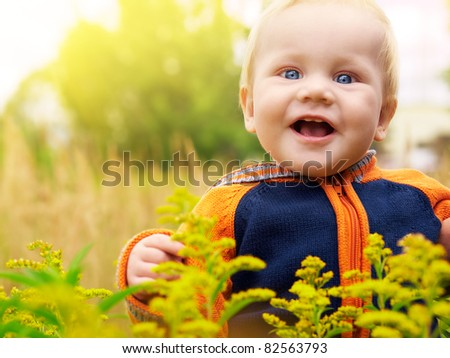 Cute baby boy in field of flowers