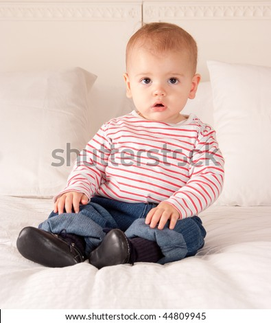 Cute baby boy in jeans and striped t-shirt sitting on a bed