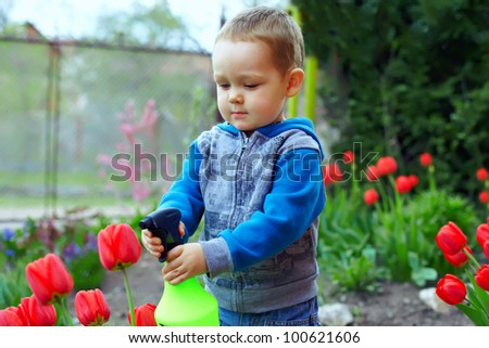 cute baby boy irrigating flowers in colorful garden