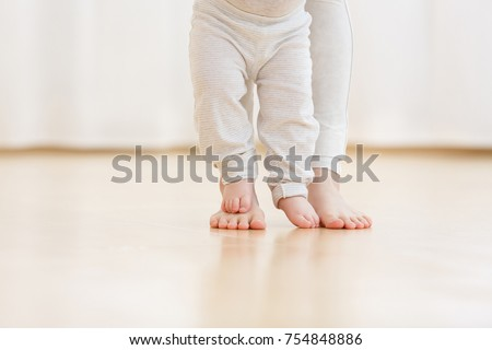 Cute baby boy learning to walk and make his first steps. mom is holding his hand. child's feet close up, copy space
