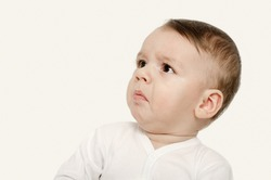 Cute baby boy looking up upset. Baby looking sad. Isolated on white.