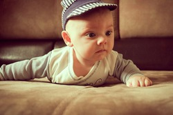 Cute baby boy lying on belly on sofa. Lifestyle portrait adorable baby. Babyhood concept, infancy.