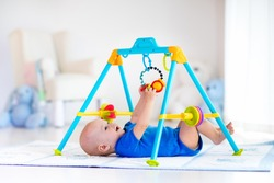 Cute baby boy on colorful playmat and gym, playing with hanging rattle toys. Kids activity and play center for early infant development. Newborn child kicking and grabbing toy in white sunny nursery.