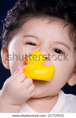 cute baby boy play with rubber duck toy