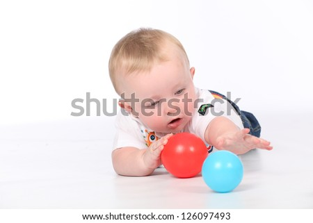 Cute baby boy playing in isolated white studio, with colorful balloons for his birthday