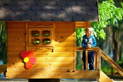 cute baby boy playing in tree house, sunny outdoor