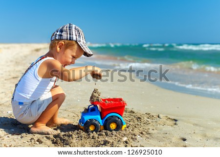 cute baby boy playing on the beach