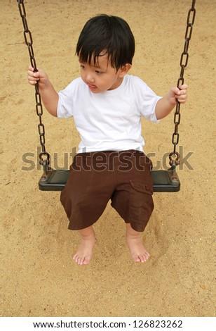 Cute baby boy playing swing