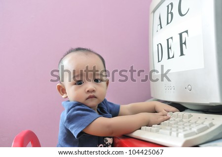 Cute baby boy playing with computer, part of early education process.