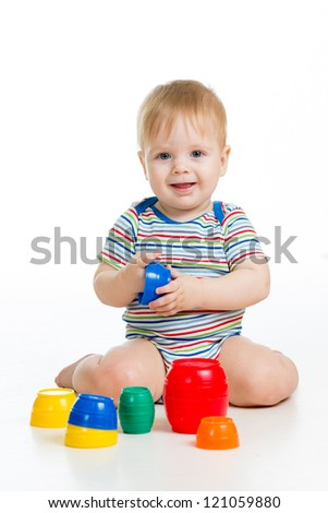 Cute baby boy playing with toys while sitting on floor, isolated over white