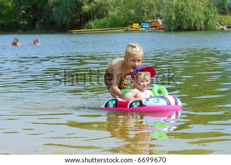 Cute baby boy plays with his sister in water. Shot in Ukraine. - stock photo