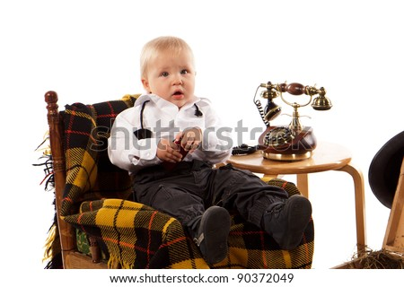 Cute baby boy sitting in a chair with retro telephone
