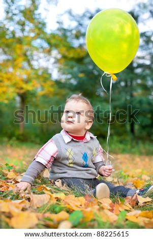 cute baby boy sitting in autumn leaves holding balloon