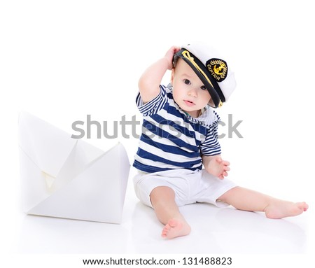 cute baby boy sitting in captain cap with ship of paper - sailor in future, over white background
