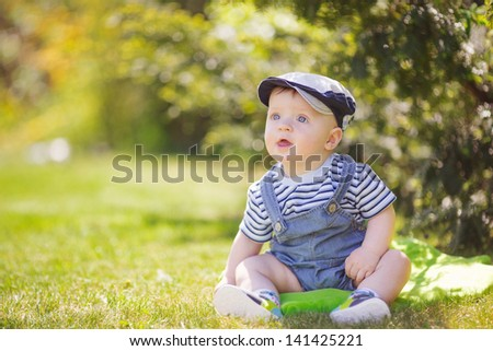 Cute baby boy sitting in summer park on the grass. Outdoor portrait