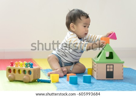 Shutterstock Cute baby boy sitting on a playmat and playing with toy by himself. Adorable eight month old child happy reach the toy.