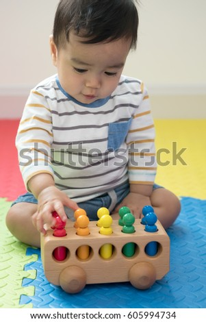 Cute baby boy sitting on a playmat and playing with toy by himself. Adorable eight Free photos Little cute - 6-month feeding spoon