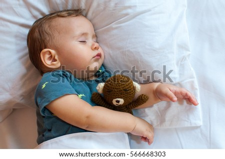 Cute baby boy sleeping on the bed at home with toy. Free space  #566668303