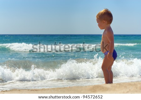 cute baby boy standing in waves on the beach