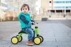 Cute baby boy wearing blue jacket and jeans playing with balance bike on outdoor background. Happy mixed race Asian-German child play outside.