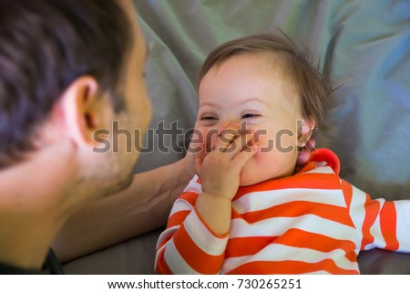 Cute baby boy with Down syndrome playing with dad on the bed in home bedroom #730265251