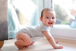 Cute baby boy with smiling face crawling on the floor next to window home. Mixed race Asian-German infant about 6-7 months old. Healthy child.